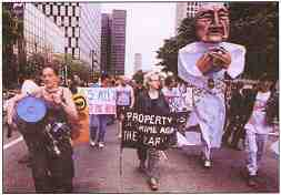 """Photo shows protesters in the street with musical instruments and a giant puppet. A sign reads, """"Property is a crime against the Earth."""""""