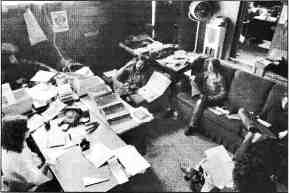 Photo shows 5 or 6 people seated on a couch and chairs in the Fifth Estate office.