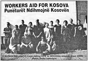 """A group photo shows about 15 people standing and sitting on the ground. A caption reads """"Workers Aid for Kosova."""""""