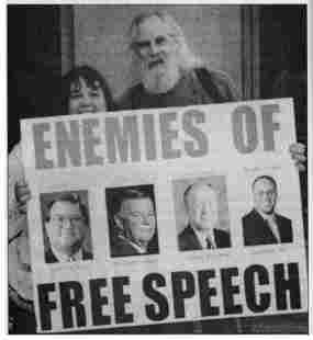 """photo of Ron Sakolsky with poster showing images of four mass media executives. Headline reads, """"Enemies of Free Speech."""""""