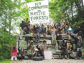 """Photo shows about 20 Earth First! protesters surrounding an upturned vehicle. A large sign reads, """"No Compromise on Native Forests."""""""